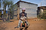 A grandmother and child sit outside their home in the Kiandutu slum. AFCIC have supplied her with the materials to build the hose when she looks after her grandchildren after loosing her daughter to HIV.