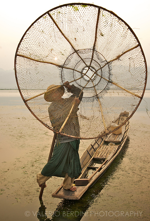 The shallow water of the lake allow the tall conical net to trap fishes inside.