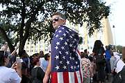 Scott Williams doning an American flag scans the large crowd of ant-White Supremacist protesters at Dallas City Hall on Saturday August 17, 2017. Hundreds gathered to protest Donald Trump and racism as well as demanding the removal of Confederate statues from downtown Dallas.