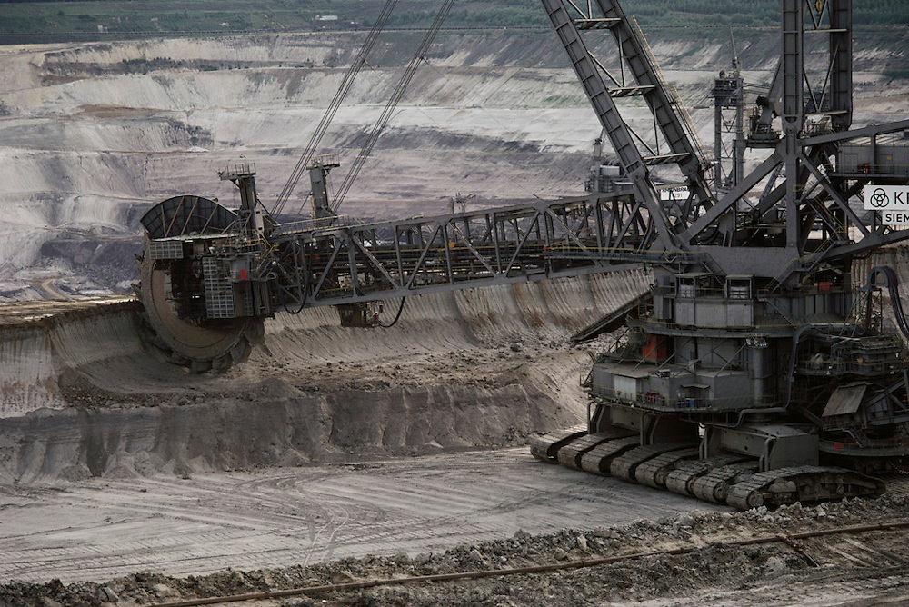 Cologne, West Germany. Coal strip mine. This huge machine is removing the overburden soil to get at the coal seam. The two operators sit in the compartment under the boom.