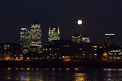 © Licensed to London News Pictures. 09/09/2014. London, UK. A supermoon is seen rising behind the Canary Wharf financial district in London on 9th September 2014.  Photo credit : Vickie Flores/LNP.