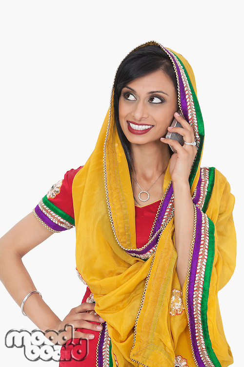 Indian woman in traditional wear answering phone call over gray background