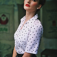 Young adult female looking at camera wearing 50's clothing