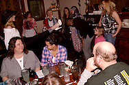 """Tammy Schaff (with hat) shows the audience members how to be models and walk on the runway during Mayhem & Mystery's production of """"Fashion Friction"""" at the Spaghetti Warehouse in downtown Dayton, Monday, March 21, 2011."""