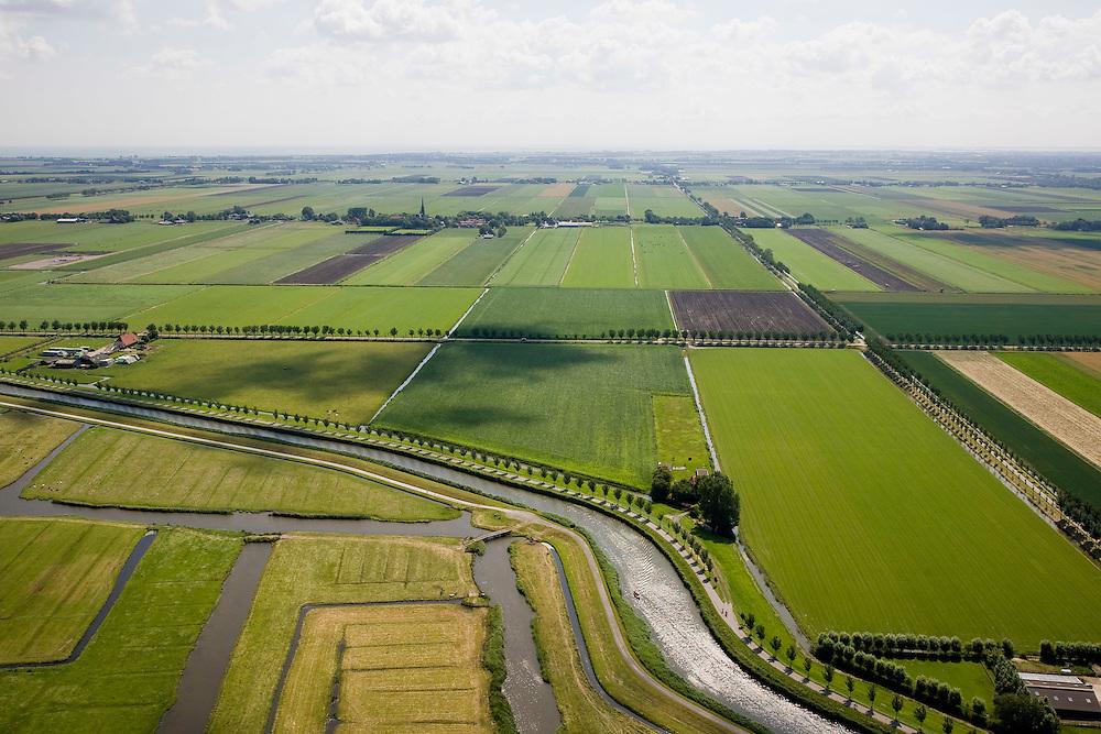 Nederland, Noord-Holland, Beemster, 14-07-2008; de beroemde geometrische verkaveling van de Beemster vormt een tegenstelling met de grillige 'lay-out' van de Eilandspolder (veenweide gebied) gelegen aan deze zijde van de Beemsterrringvaart; op het tweede plan de kerkspits in Noordbeemster en in het verschiet - aan de verre horizon - het IJsselmeer; de polder Beemster, een 17e eeuwse droogmakerij, maakt deel uit van het wereld erfgoed (Unesco werelderfgoedlijst, erfgoedlijst); raster, kavel, symmetrie, geometrie. .luchtfoto (toeslag); aerial photo (additional fee required); .foto Siebe Swart / photo Siebe Swart