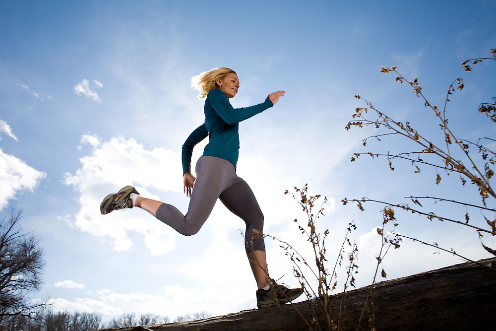 A woman is running outdoors on top of a log and is backlit by the sun.