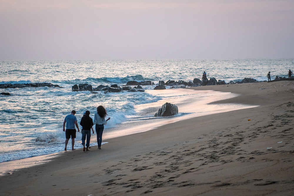 A group of people walk alongside the water at dusk on a beach in Monrovia, Liberia