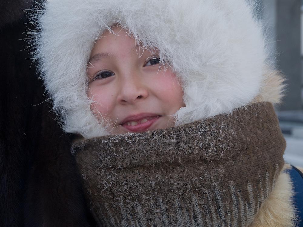 Jakutisches Maedchen mit Kopfbedeckung gesch&uuml;tzt gegen die extreme Kaelte in der Innenstadt von Jakutsk. Jakutsk wurde 1632 gegruendet und feierte 2007 sein 375 jaehriges Bestehen. Jakutsk ist im Winter eine der kaeltesten Grossstaedte weltweit mit durchschnittlichen Winter Temperaturen von -40.9 Grad Celsius. Die Stadt ist nicht weit entfernt von Oimjakon, dem Kaeltepol der bewohnten Gebiete der Erde.<br /> <br /> Yakut girl protected with headgears against the extrem climate  in the city center of Yakutsk. Yakutsk was founded in 1632 and celebrated 2007 the 375th anniversary - billboard announcing the celebration. Yakutsk is a city in the Russian Far East, located about 4 degrees (450 km) below the Arctic Circle. It is the capital of the Sakha (Yakutia) Republic (formerly the Yakut Autonomous Soviet Socialist Republic), Russia and a major port on the Lena River. Yakutsk is one of the coldest cities on earth, with winter temperatures averaging -40.9 degrees Celsius.