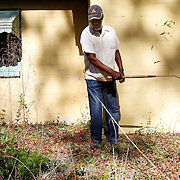 Bob Johnson, of St. Helena Island, uses a swing blade to tidy up the lawn at a home off of Sea Island Pkwy on April 9, 2014.