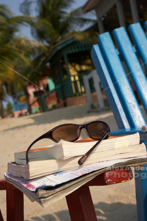 Belize, Central America - Sunglasses and a pile of books on a beach chair by the beach houses on the end of the Placencia spit