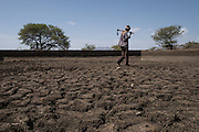 """Hamusit, Ethiopia - 17.05.16  - Farmer Berara Gebrie, 55, walks in a 13-year-old dam in Hamusit ward, East Belessa district, Ethiopia on May 17, 2016. The dam was built by CBM's partner, the Organization for Rehabilitation and Development in Amhara (ORDA) but has fallen into disrepair after years of use. Now, with rains approaching, it's important to de-silt over 4 meters of dirt from the dam, so it can be used by farmers like Berara, who promises to make sure it's used properly and maintained well. """"This dam was a very crucial water resource for us. We'd bathe here, bring our cattle here and even use the water for our home use,"""" says Gebrie.    Photo by Daniel Hayduk"""