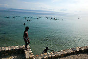 Despite problems causing polluted, bacteria-filled water in Haiti, locals still spend time swimming.