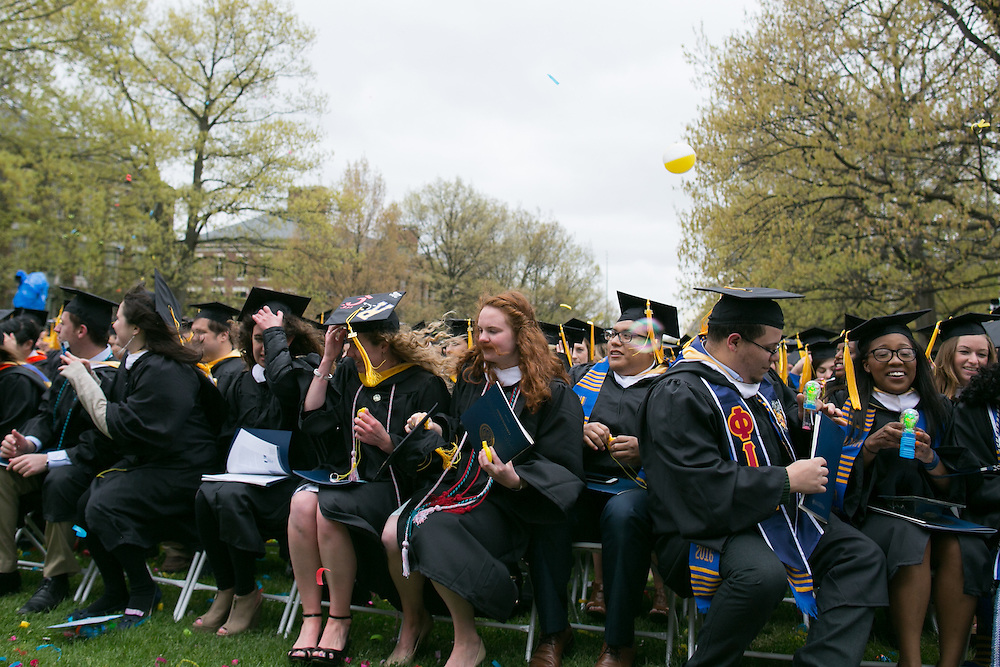 Graduates hold onto their caps as the wind gusts at the University of Rochester's Commencement ceremony in Rochester on Sunday, May 15, 2016.