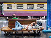 16 APRIL 2014 - BANGKOK, THAILAND: A man sleeps on a bench before boarding a train to take him home after the Songkran holiday. Thai highways, trains and buses were packed Wednesday as Thais started returning home after the long Songkran break. Songkran is normally three days long but this year many Thais had at least an extra day off because the holiday started on Sunday, so many Thais started traveling on Friday of last week.    PHOTO BY JACK KURTZ