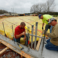 THOMAS WELLS | BUY at PHOTOS.DJOURNAL.COM<br /> Hooker Construction workers John Logan, from left, Danny Carl and Roberts Stevens begin taking down the concrete forms around the base of the new storm shelter under constructin at North Pontotoc High School on Monday.