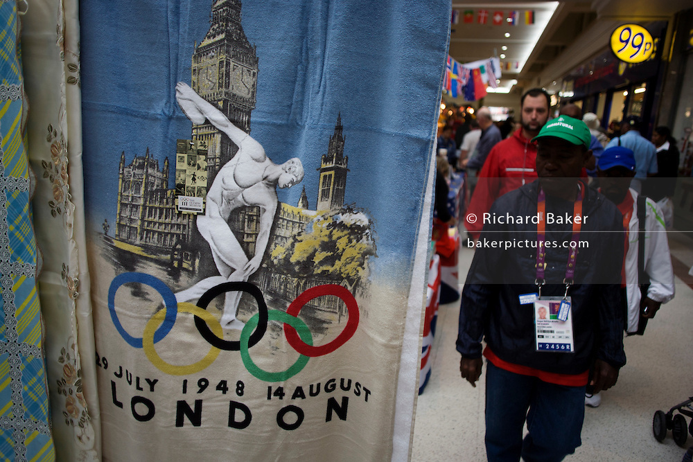 In the local community Stratford Centre shopping mall in East London, we see official Olympic merchandising on sale during the London 2012 Olympics, the 30th Olympiad. A few hundred metres from the giant Westfield plaza complex that acts as a gateway to the main Olympic arenas, this market outdates the newer development where similar souvenirs can be bought for up to twice the prices offered by the stall holder. Cashions are £10 (Pounds) and duvet covers (bedding) are £20.
