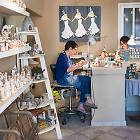 Artisians paint ceramic figurines at Atelier Arterra, a workshop and store located in the Panier neighborhood of Marseille, France, that sells traditional painted ceramic figurines known as santons.