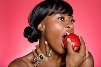 Close up of woman biting an apple over colored background