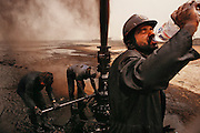 Oil well fire specialists of Wild Well Control, Inc. of Texas cap a Kuwait oil well after extinguishing one of the 700 fires that raged in the fields during the Gulf War. Working in high winds with ambient temperature well over 100 degrees F, workers dressed in Nomex suits drank 10-20 liters of water a day. (July, 1991).