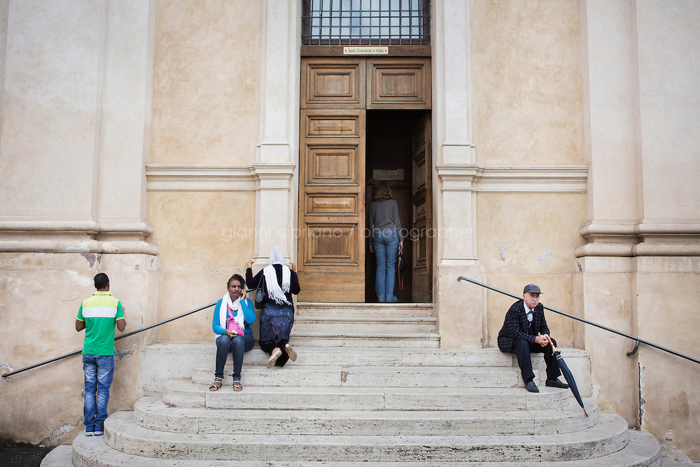 ROME, ITALY - 16 NOVEMBER 2014: (L-R) An Italian man sits on the stairs of the Church of Saints Joachim and Anne, as Ethiopian refugees of the Orthodox Tewahedo Church pray, in the Monti neighborhood in Rome, Italy, on November 16th 2014.