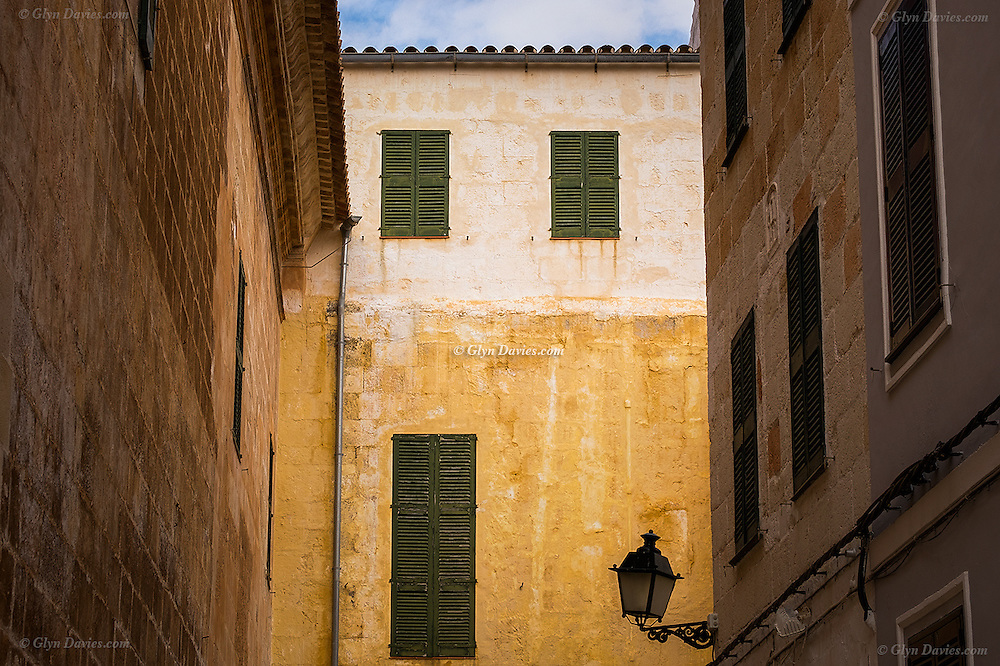Beautiful old buildings in the unspoilt old town of Ciutadella (once the capital town) of the Balearic island of Menorca. Narrow streets, tall buildings, small windows and many shutters are characteristic features of these streets.