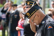 Middletown, New York - A veteran bows his head and salutes at Thrall Park during the Middletown-Town of Wallkill Memorial Day ceremonies on  May 25, 2015.