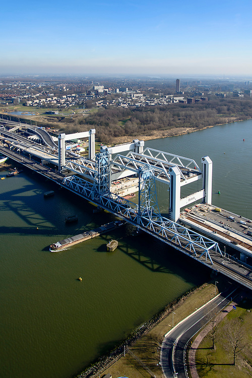 Nederland, Zuid-Holland, Rotterdam, 18-02-2015; bouw van de nieuwe Botlekbrug. De brug over de Oude Maas is een hefbrug, een van de twee brugdelen in geheven toestand. De oude brug met heftorens in de voorgrond, een schip vaart onder de oude brug door.<br /> Construction of the new Botlek bridge. The bridge over the Oude Maas is a vertical-lift bridge or lift bridge, one of the two bridge sections raised. <br /> luchtfoto (toeslag op standard tarieven);<br /> aerial photo (additional fee required);<br /> copyright foto/photo Siebe Swart