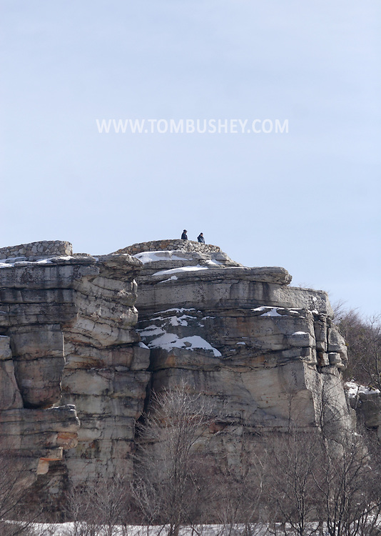 Cragsmoor, NY - Two hikers stand on the cliffs at Sam's Point Dwarf Pine Ridge Preserve in the Shawangunks on a winter day. Feb. 29, 2008.