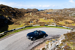 Single track road and car on the North Coast 500 scenic driving route in Assynt northern Scotland, UK
