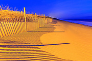 A sand fence lit by Avalon Pier's parking lot light, casting shadows at twilight on the beach at kill Devil Hills North Carolina.
