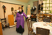 Virginia, a volunteer at the museum, wears a recreation of a period dress.