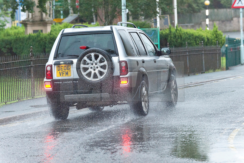 © Licensed to London News Pictures. 14/08/2019. Builth Wells, Powys, UK. A vehicle drives through surface water in Builth Wells in Powys after heavy rain last night. Photo credit: Graham M. Lawrence/LNP