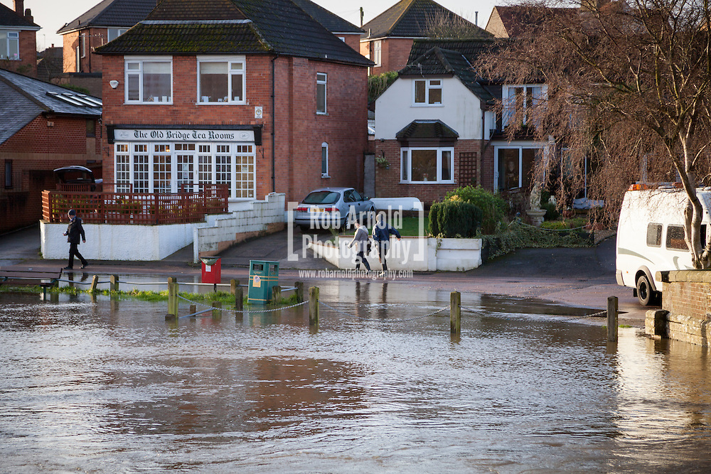 03/01/2014. Christchurch, Dorset, UK. People make their way past flood water on Old Bridge Road in Christchurch, Dorset, UK on a day that will bring the risk of flooding to much of the south west of England & Wales. Photo by Rob Arnold
