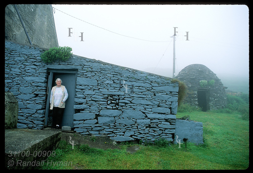 Woman stands at her door to collect cash for seeing Fahan Group beehive huts on her farm; Dingle Ireland