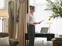 Business woman reading document in home office side view