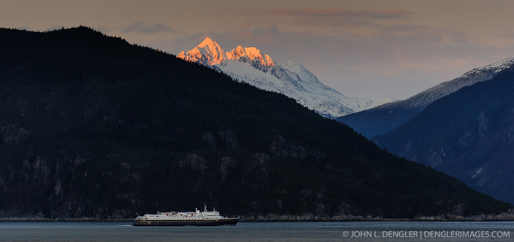 The final rays of the sun at sunset baths mountain tops in light as an Alaska Marine Highway System ferry travels down the Chilkoot Inlet of the Lynn Canal in this photo taken just outside Haines, Alaska.