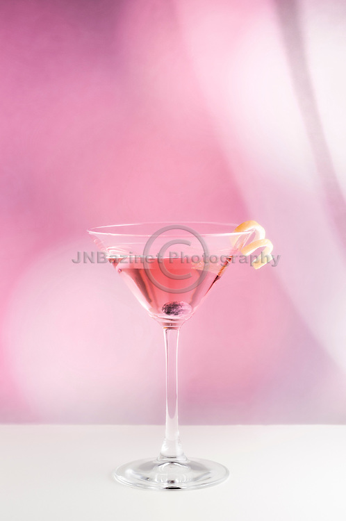 Pink cocktail in martini glass with curling lemon rind set against soft pink background.