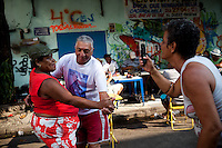 Residents dance samba during a street party in Complexo da Mare, Rio de Janeiro, Brazil, on Saturday, April 27, 2013. Complexo da Mare, is a complex of 16 communities, in the north zone of Rio de Janeiro. It is the largest complex of favelas with 130,000 residents. It is targeted for pacification as the city prepares for the 2014 World Cup and the 2016 Olympics. Four factions run the complex -  three drug gangs and the militia. The rival gangs fight for control of the drug trade. Although crime is low in the favelas by rule  of law enforced by the gangs, cross-fire shootings and gang violence is often high. Neighborhood associations are an integral part of community development within Mare, making up for a lack of government assistance.
