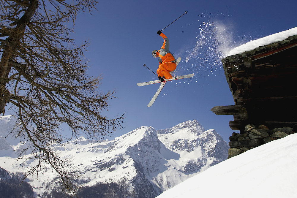 Sport. Skier jumps from a chalet roof in the Monterosa ski region, Italy