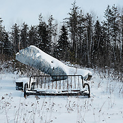 A snow-covered sofa frame and scrap metal at a sand quarry at the Ochiichagwe'Babigo'Ining Ojibway Nation (also known as the Dalles First Nation) in Northern Ontario, Canada on 14 December 2016.