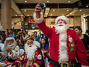 17 SEPTEMBER 2015 - BANGKOK, THAILAND: SHUKO YAMAMOTO, a Santa Claus from Japan, takes pictures of the Santa Claus pageant in Bangkok. Twenty-six Santa Clauses from around the world are in Bangkok for the first World Santa Claus Congress. The World Santa Claus Congress has been an annual event in Denmark since 1957. This year's event, hosted by Snow Town, a theme park with a winter and snow theme, hosted the event. There were Santas from Japan, Hong Kong, the US, Canada, Germany, France and Denmark. They presented gifts to Thai children and judged a Santa pageant. Thailand, a Buddhist country, does not celebrate the religious aspects of Christmas, but Thais do celebrate the commercial aspects of the holiday.    PHOTO BY JACK KURTZ