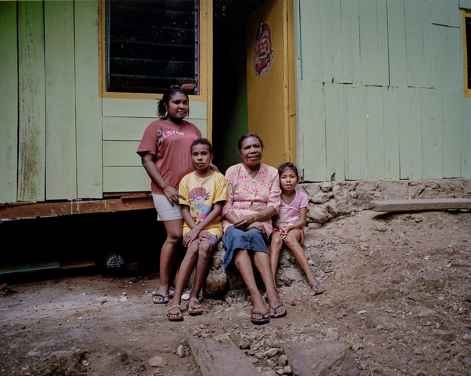 Portrait Series.<br /> <br /> A family portrait of Mama Yuli (48) with her daughters Aldofina (22) and Sela (12) and granddaughter, Anace (8).  <br /> <br /> Mama Yuli was infected with HIV from her husband who later died. At one point she weighed only 30kg (66lbs) but she is now healthy to work and support her family. Although ARV is free in Papua, less than 12% of those infected with HIV/AIDS are undergoing Anti-Retroviral Therapy (ART). Mama Yuli opened her status by making testimony to the public in order to encourage others living with HIV/AIDS to take their medication regularly and prove to them that they could still provide for their family and live a productive life.