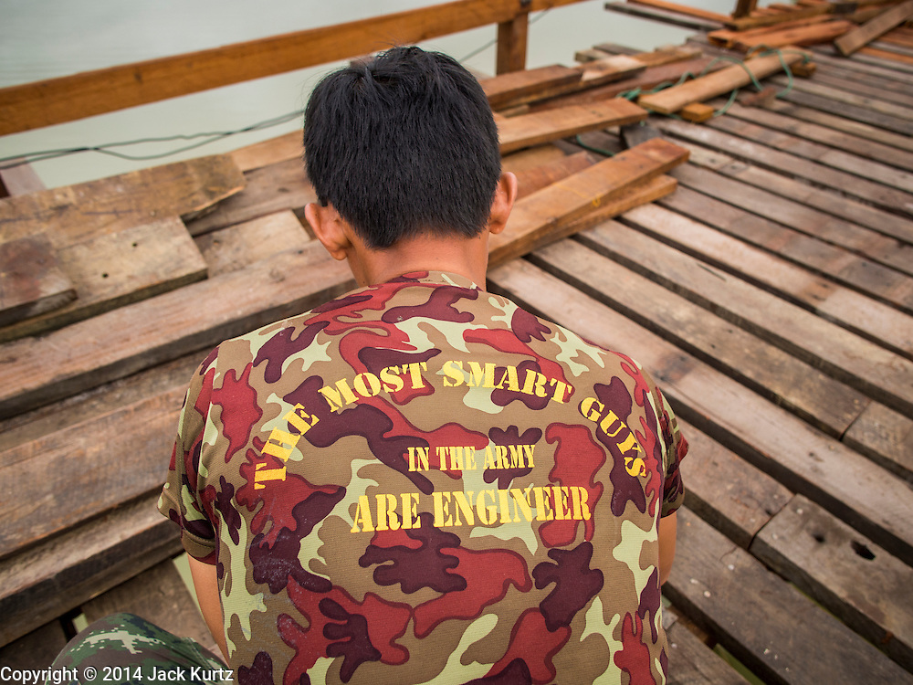 16 SEPTEMBER 2014 - SANGKHLA BURI, KANCHANABURI, THAILAND:  A soldier in the Royal Thai Army works on the Mon Bridge. The 2800 foot long (850 meters) Saphan Mon (Mon Bridge) spans the Song Kalia River. It is reportedly second longest wooden bridge in the world. The bridge was severely damaged during heavy rainfall in July 2013 when its 230 foot middle section  (70 meters) collapsed during flooding. Officially known as Uttamanusorn Bridge, the bridge has been used by people in Sangkhla Buri (also known as Sangkhlaburi) for 20 years. The bridge was was conceived by Luang Pho Uttama, the late abbot of of Wat Wang Wiwekaram, and was built by hand by Mon refugees from Myanmar (then Burma). The wooden bridge is one of the leading tourist attractions in Kanchanaburi province. The loss of the bridge has hurt the economy of the Mon community opposite Sangkhla Buri. The repair has taken far longer than expected. Thai Prime Minister General Prayuth Chan-ocha ordered an engineer unit of the Royal Thai Army to help the local Mon population repair the bridge. Local people said they hope the bridge is repaired by the end November, which is when the tourist season starts.   PHOTO BY JACK KURTZ