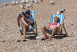 © Licensed to London News Pictures. 13/06/2014. Brighton, UK. A couple sunbathing on Brighton beach.  Today, Friday 13th June is expected to be the hottest day of the year so far with temperatures hitting nearly 30C at some locations. Brighton beach is slowly filling up with sunbathers and people wanting to relax by the beach. Photo credit : Hugo Michiels/LNP