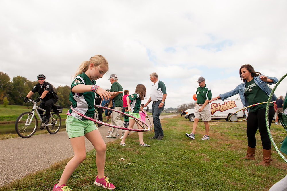 Mia Pittaway, left, and her sister Isabella, center, play with hula-hoops on the bike path outside the College of Business tent during the homecoming 2013 tailgate party. Photo by Elizabeth Held