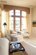 Sunlit floor to ceiling windows in cream living room interior