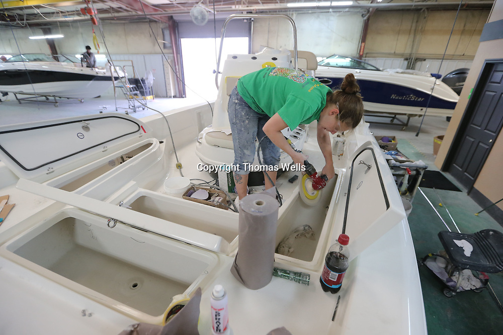 Cindy Wilson buffs out a storage bin as boats are completed at Nauticstar boat in Amory.