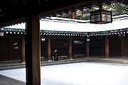 A visitor sits in the forecourt of Meiji Jingu Shrine after the year's first snowfall in Tokyo, Japan on 02 Feb. 2010.