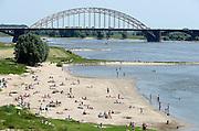 Nederland, Nijmegen, 8-7-2013Warme zomerse dag op het Waalstrand van Lent tegenover Nijmegen, makkelijk te bereiken via de fietsbrug die hier ligt. Het zwemmen in de rivier de waal, rijn, is gevaarlijk vanwege de veraderlijke stroming en de drukke scheepvaart.Foto: Flip Franssen