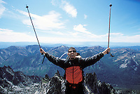 A man celebrating as he comes to the summit of Little Annapurna Mountain in the Central Cascades range in Washington State, USA.
